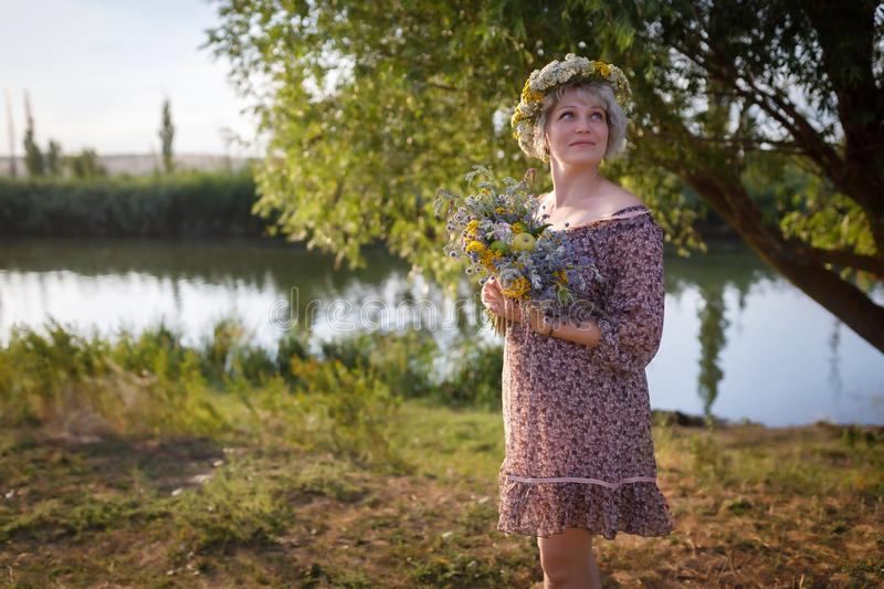 Cute caucasian woman stands on the bank of the river with a bouquet of wild flowers at sunset stock photos