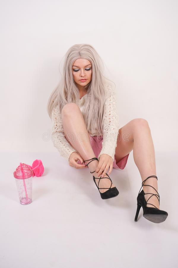 Cute caucasian young blonde girl in a knitted sweater is sitting on the floor and wearing high heel black shoes on her feet on whi. Te studio background stock photo