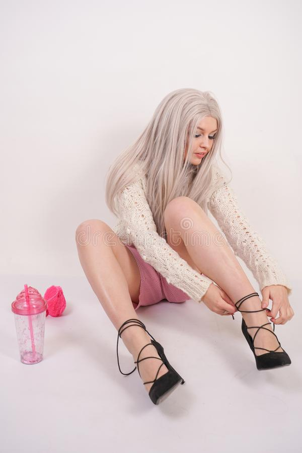 Cute caucasian young blonde girl in a knitted sweater is sitting on the floor and wearing high heel black shoes on her feet on whi. Te studio background royalty free stock photography