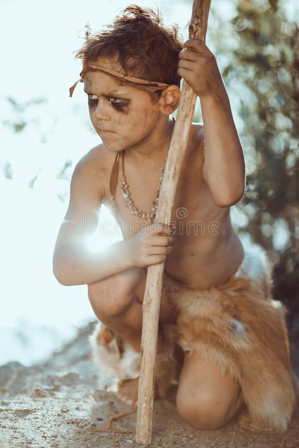 Cute caveman, manly boy with staff hunting outdoors. Ancient warrior. Cute caveman, manly boy with staff hunting. Prehistoric tribal boy outdoors on nature stock image