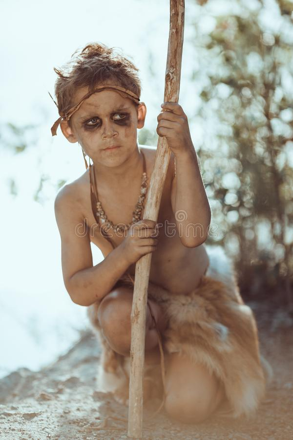 Cute caveman, manly boy with staff hunting outdoors. Ancient warrior. Cute caveman, manly boy with staff hunting. Prehistoric tribal boy outdoors on nature stock images