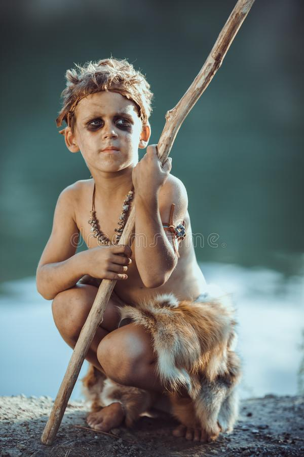 Cute caveman, manly boy with staff hunting outdoors. Ancient warrior. Cute caveman, manly boy with staff hunting. Prehistoric tribal boy outdoors on nature stock photography