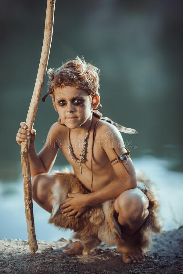 Cute caveman, manly boy with staff hunting outdoors. Ancient warrior. Cute caveman, manly boy with staff hunting. Prehistoric tribal boy outdoors on nature royalty free stock photo
