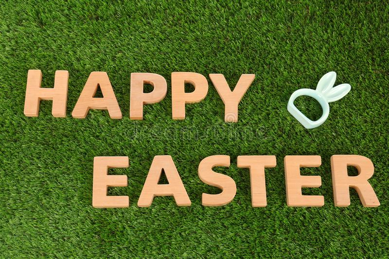 Cute ceramic bunny ears and text HAPPY EASTER made of wooden letters on green grass royalty free stock image
