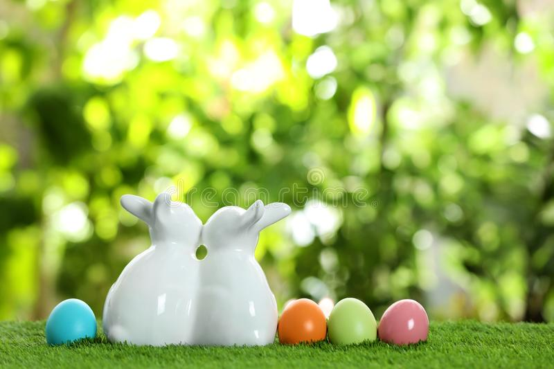 Cute ceramic Easter bunnies and dyed eggs on grass against blurred background, space for text stock photo