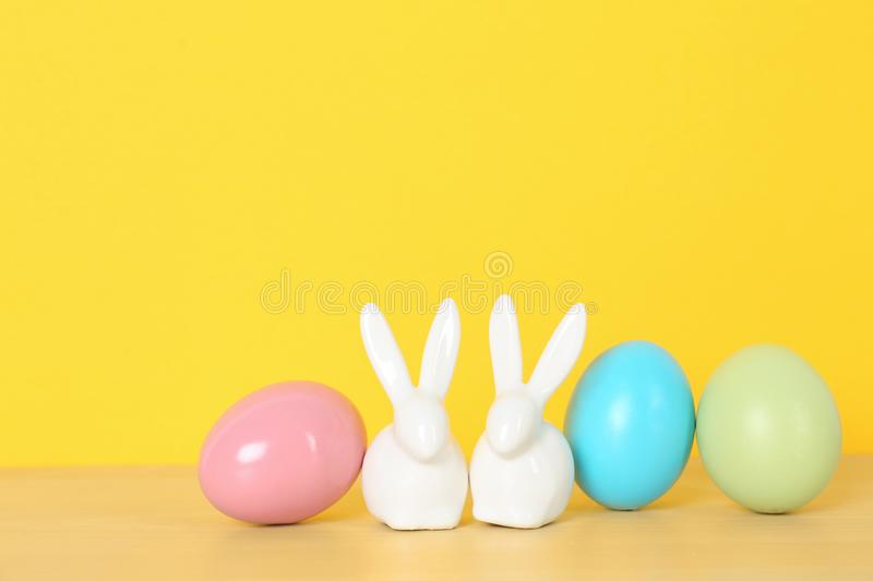 Cute ceramic Easter bunnies and dyed eggs on table against color background stock image