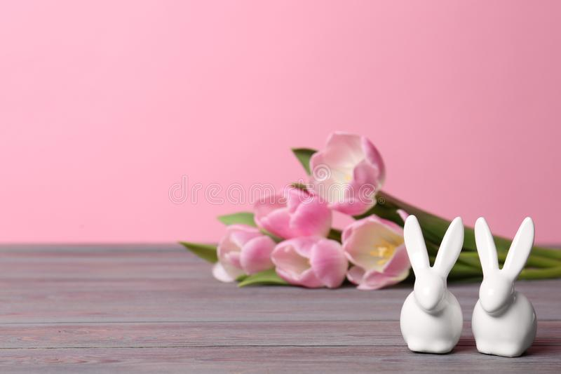 Cute ceramic Easter bunnies and spring tulips on table against color background, space for text stock photo