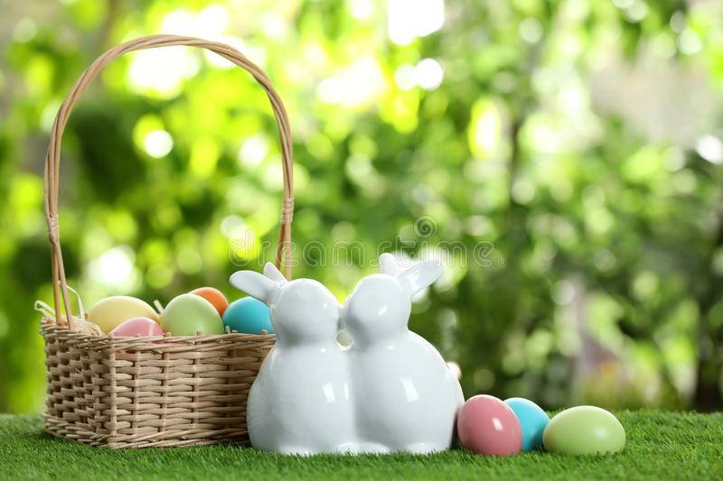 Cute ceramic Easter bunnies with wicker basket and dyed eggs on green grass against blurred background stock photography