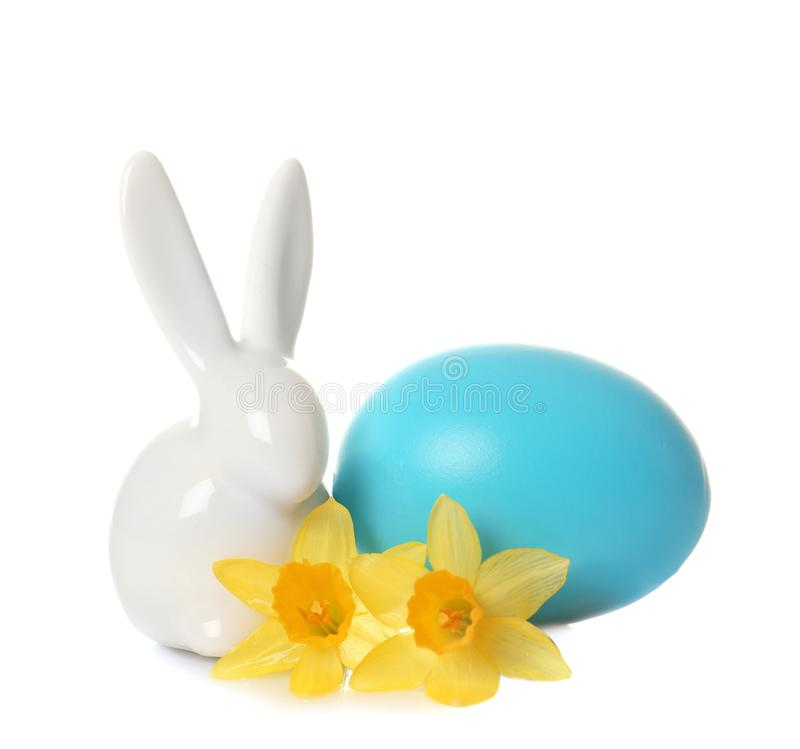 Cute ceramic Easter bunny with flower and dyed egg stock photo