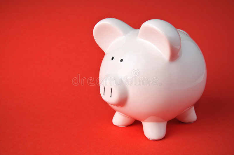 Cute Ceramic Piggy Bank on Red Background royalty free stock photography