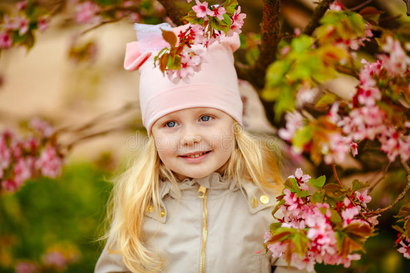 A cute charming blonde girl with lush hair on a pink sakura spring background royalty free stock photography
