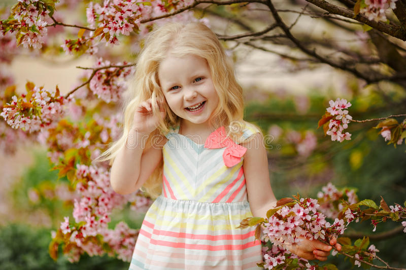 A cute charming blonde girl with lush hair smiling on a pink sakura spring background stock image