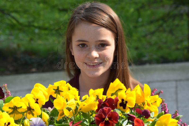 Teenage girl and yellow violas. Cute charming teenager girl with a lot of freckles and long  brown hair in the garden royalty free stock photo