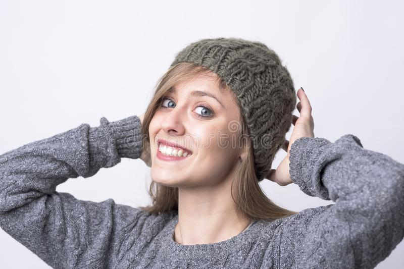 Cute charming young woman trying on gray knitted beanie cap smiling at camera stock images
