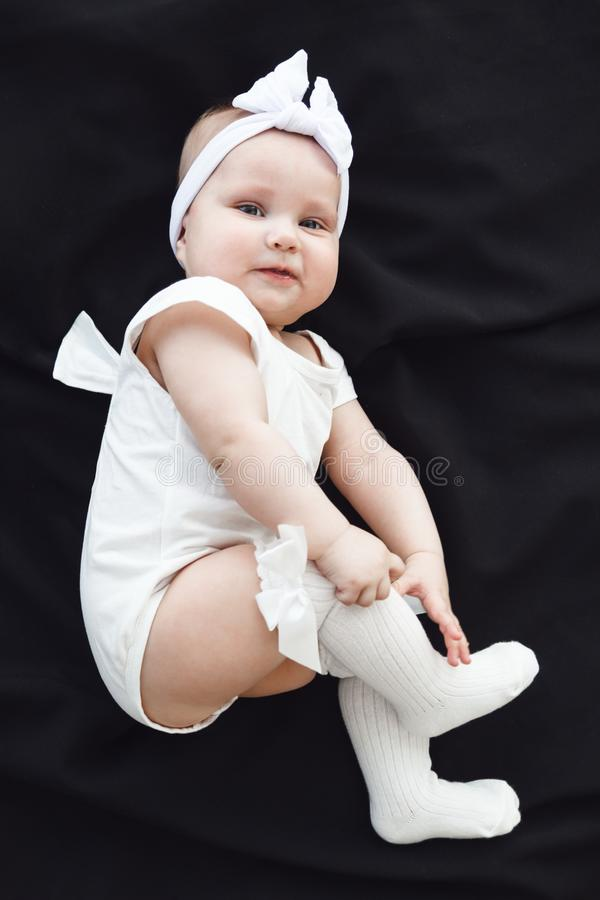 Cute cheerful baby girl wearing white clothes and headband on black background royalty free stock photo