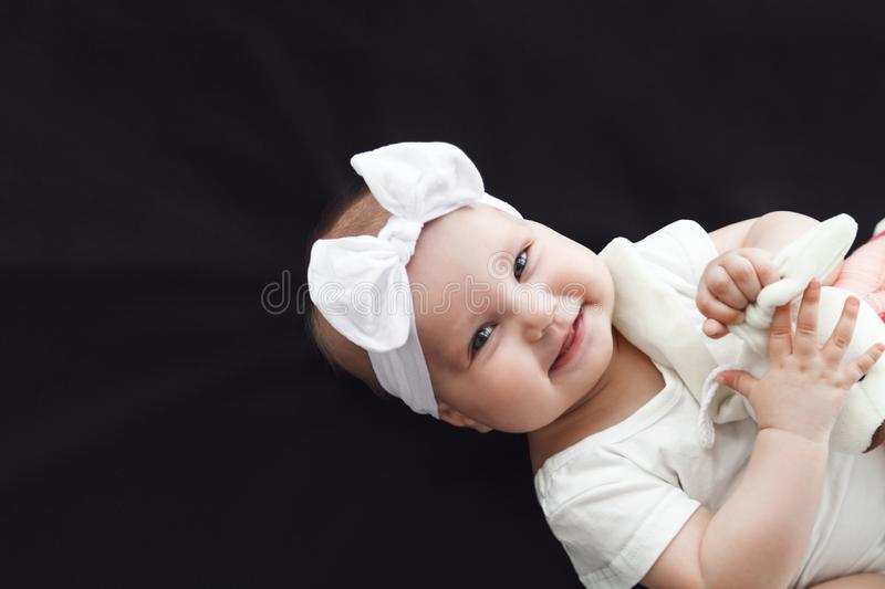 Cute cheerful baby girl wearing white clothes and headband on black background royalty free stock photos