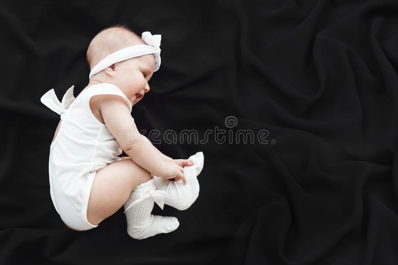 Cute cheerful baby girl wearing white clothes and headband on black background stock photos