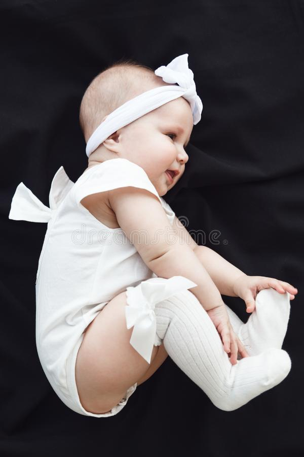 Cute cheerful baby girl wearing white clothes and headband on black background royalty free stock photography