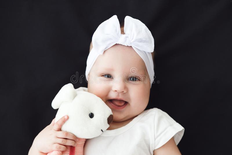 Cute cheerful baby girl wearing white clothes with rabbit toy on black background royalty free stock images