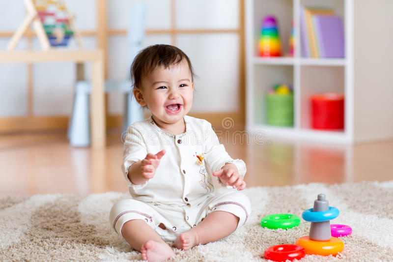 Cute cheerful baby playing with colorful toy at home stock image