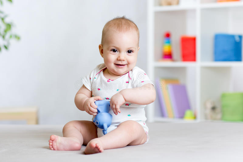 Cute cheerful baby playing with toy at home royalty free stock photos