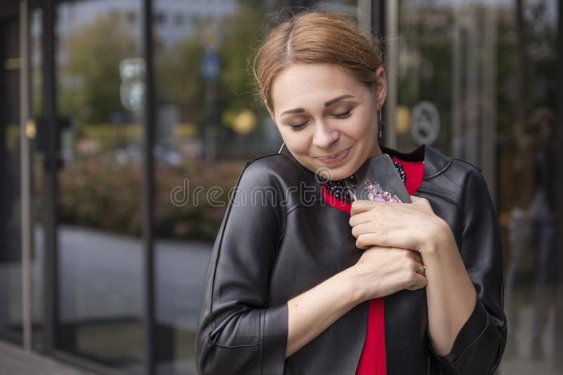 Cute cheerful caucasian woman on european street. She wear stylish outfit and work on her phone stock photography