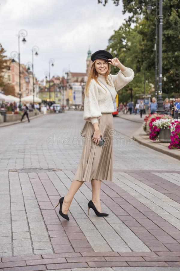 Cute cheerful caucasian woman walking on european street. She wear stylish outfit royalty free stock photography