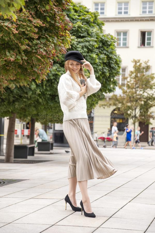 Cute cheerful caucasian woman walking on european street. She wear stylish outfit stock images