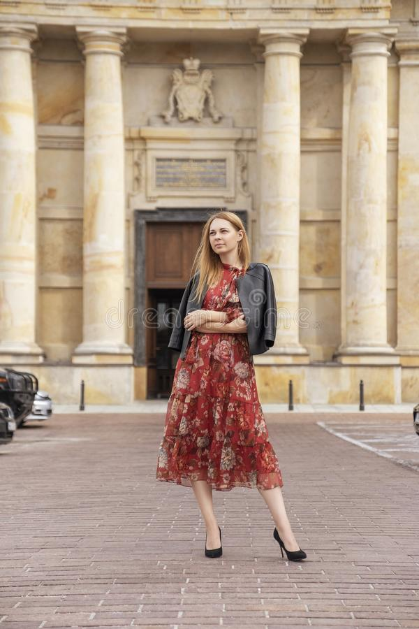 Cute cheerful caucasian woman walking on european street. She wear stylish outfit royalty free stock image
