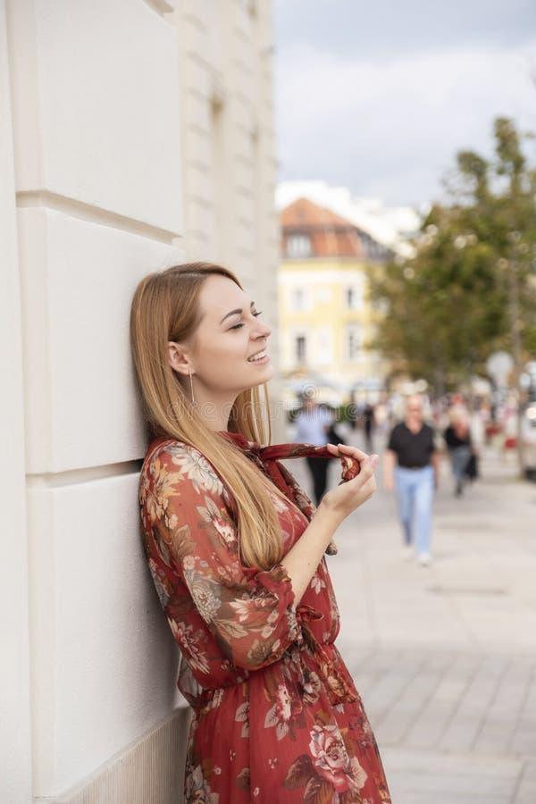 Cute cheerful caucasian woman walking on european street. She wear stylish outfit stock photos