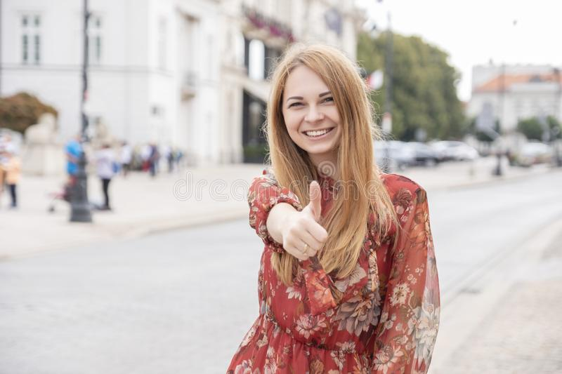 Cute cheerful caucasian woman walking on european street. She wear stylish outfit and make thumb up with her hand royalty free stock photo