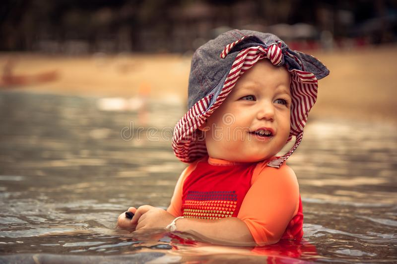 Cute cheerful child girl enjoy swimming in sea during beach holidays stock photo