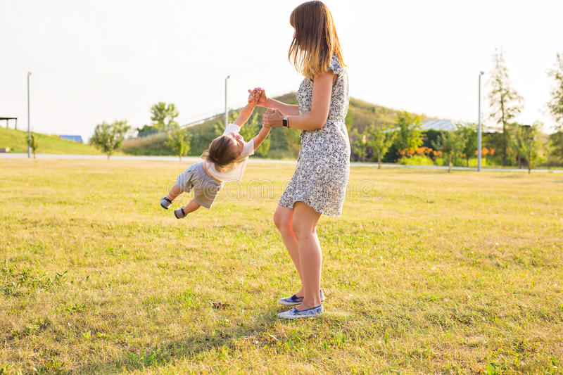 Cute cheerful child with mother play outdoors in park royalty free stock photos