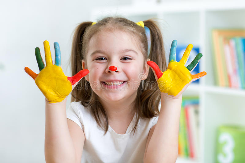 Cute cheerful child with painted hands and face royalty free stock photography