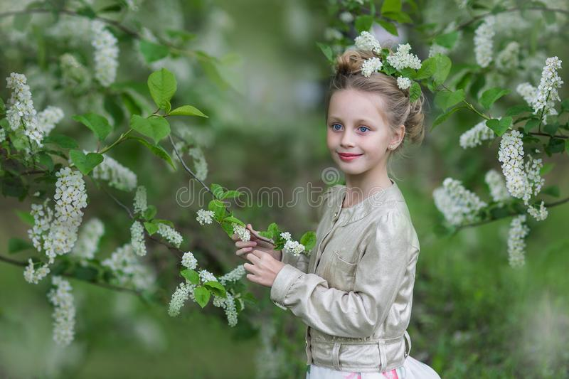 Cute cheerful girl in the flowered cherry-tree garden stock images