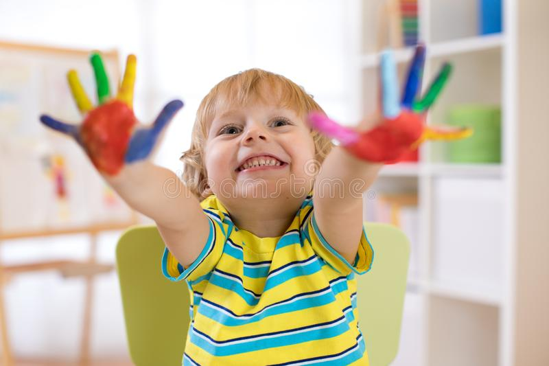 Cute cheerful kid boy showing hands painted in bright colors stock image
