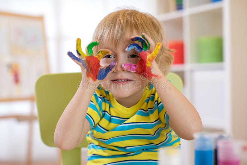 Cute cheerful kid with hands painted in bright colors royalty free stock image