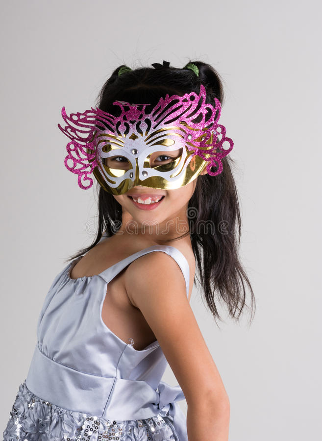 Cute, cheerful little girl in mask stock images
