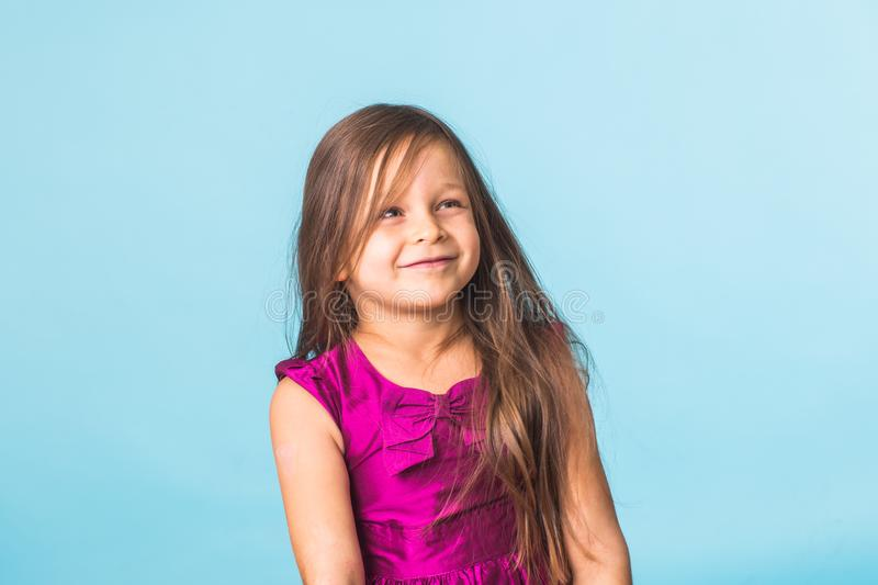 Cute cheerful little girl portrait, isolated on blue background royalty free stock photos
