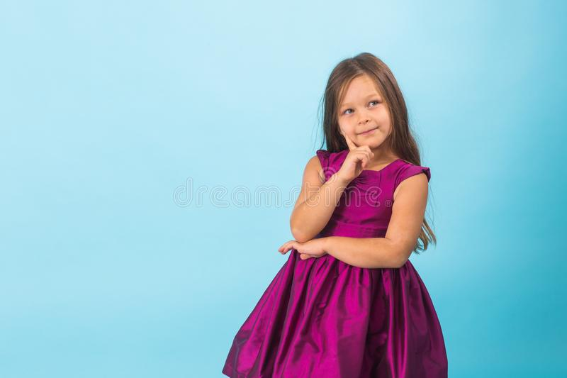 Cute cheerful little girl portrait, isolated on blue background with copy space royalty free stock photo
