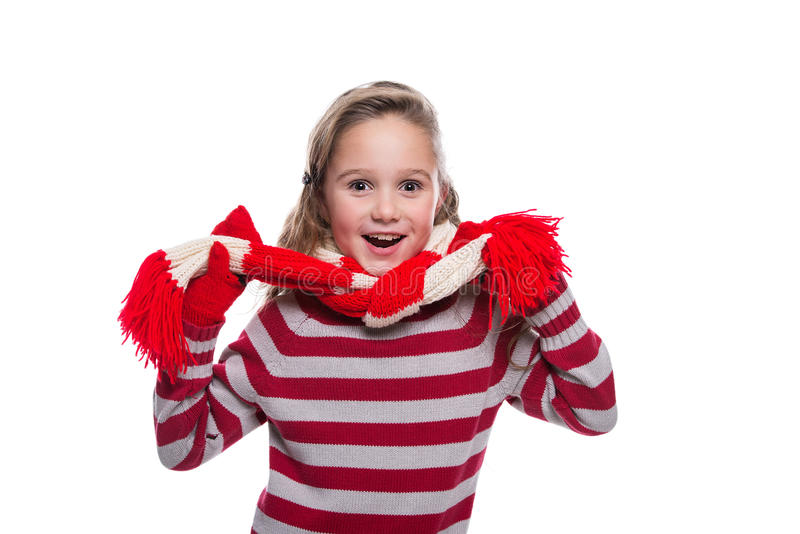 Cute cheerful little girl wearing striped knitted sweater, scarf and mittens isolated on white background. Winter clothes. royalty free stock images