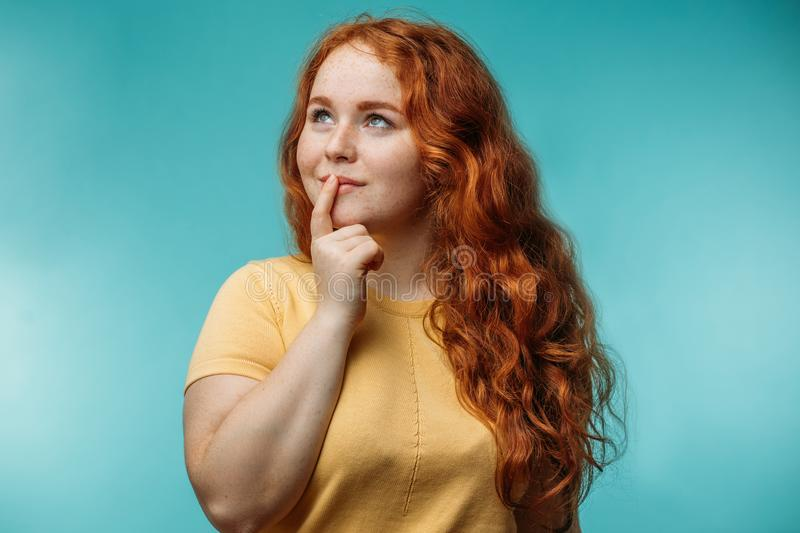 Cute cheerful redhead young girl over blue background with wondering face. stock photography