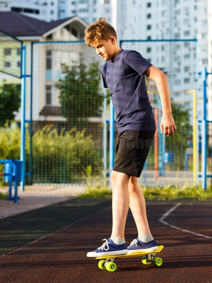 Cute cheerful smiling Boy in blue t shirt sneakers riding on yellow skateboard. Active urban lifestyle of youth, training, hobby,. Activity concept. Active stock image