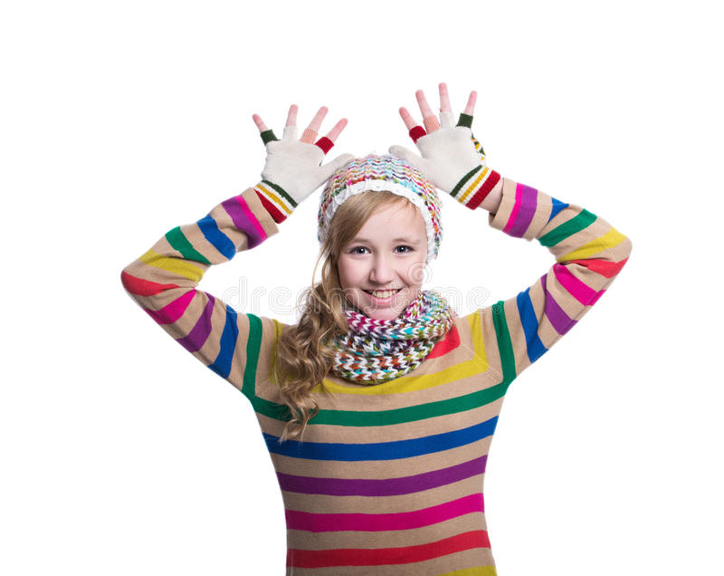 Cute cheerful teenage girl wearing colorful striped sweater, scarf, gloves and hat isolated on white background. Winter clothes. stock image