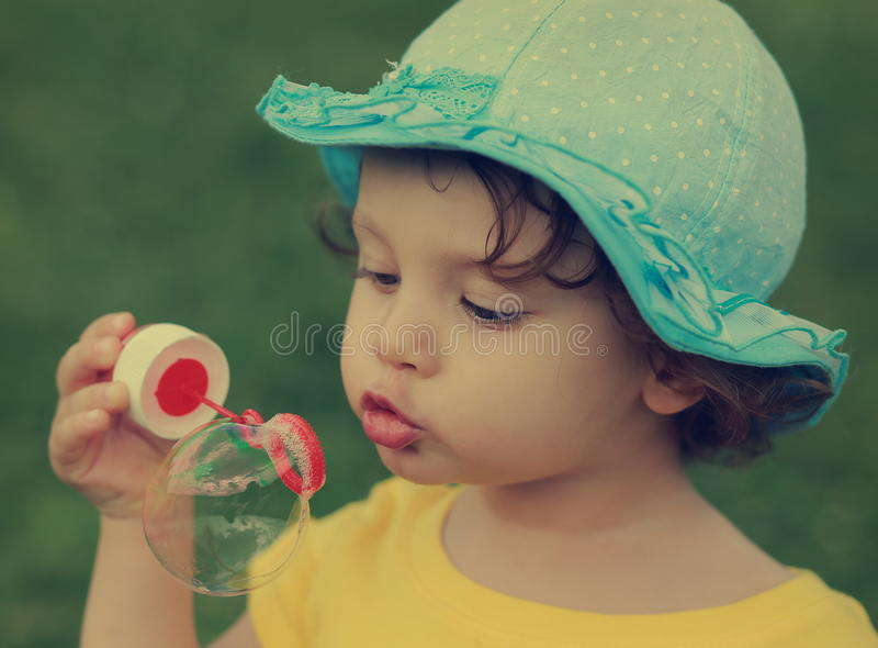 Cute child blowing big bubble. stock image