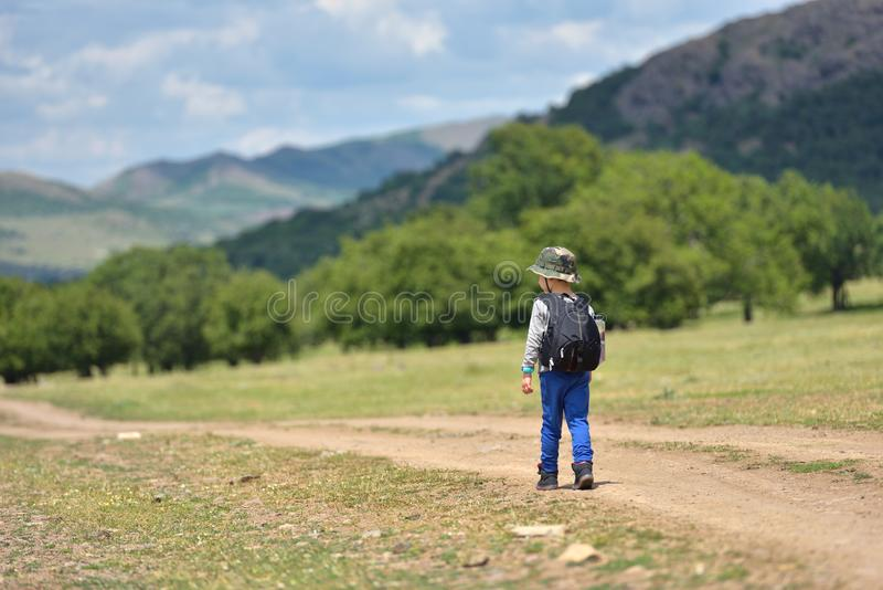 Cute child boy with backpack walking on a little path in mountains. Hiking kid.  stock image
