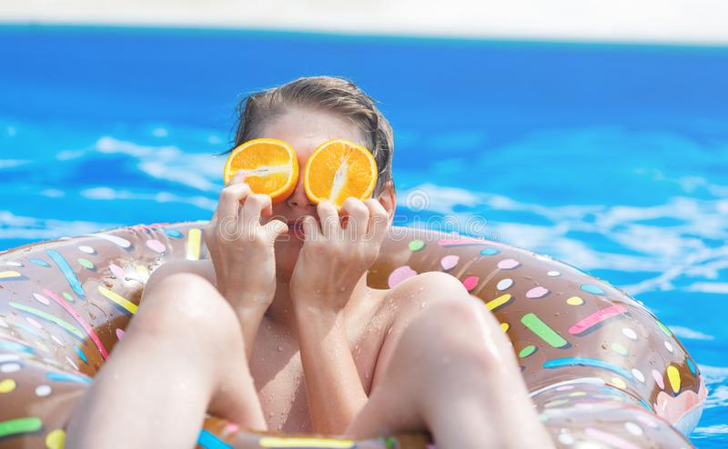 Cute child boy on funny inflatable donut float ring in swimming pool with oranges. Teenager learning to swim. Have fun in outdoor pool at resort. Water toys stock photography