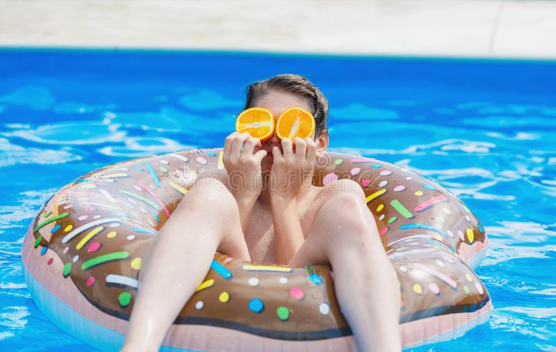 Cute child boy on funny inflatable donut float ring in swimming pool with oranges. Teenager learning to swim. Have fun in outdoor pool at resort. Water toys royalty free stock photos