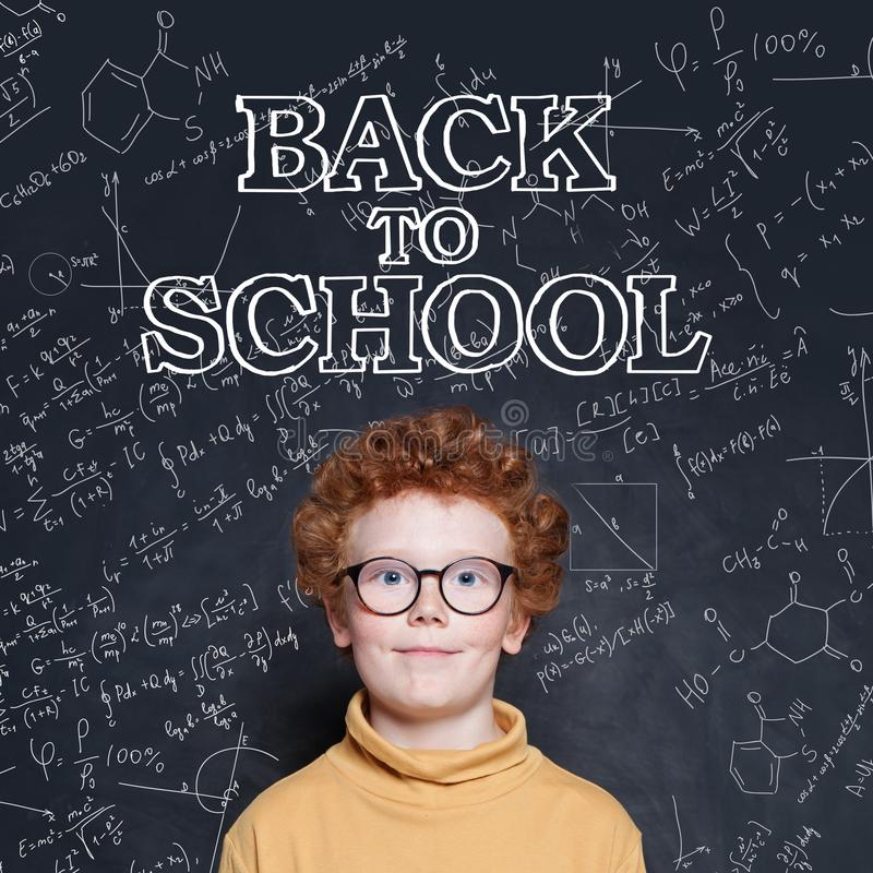 Cute child boy with ginger hair in classroom on chalkboard background. Back to school concept royalty free stock photography