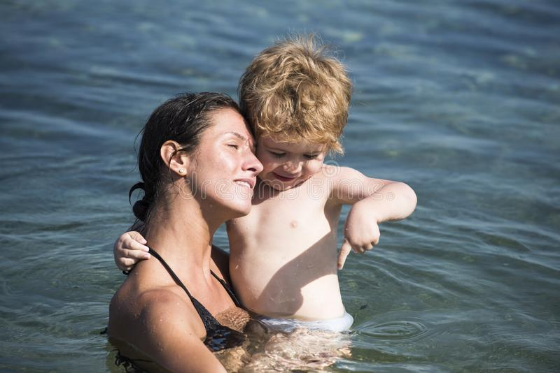 Cute child boy play with water in ocean, sea. Motherhood concept. Mother carries son in hands, hugs child. Mom and kid. With smiling faces spend time together stock photography